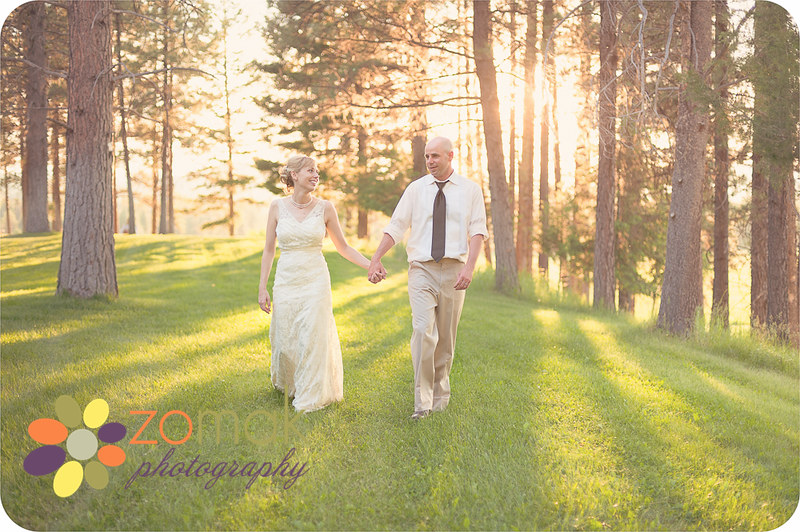 Bride and groom walk hand in hand as the sun sets behind them after their Beautiful Seeley Lake wedding