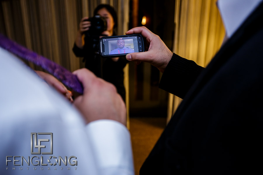 Groom and best man watching a YouTube video on how to tie a bowtie