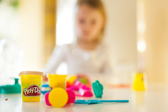 A Can of play-doh surrounded by play-doh tools and a child in the background.