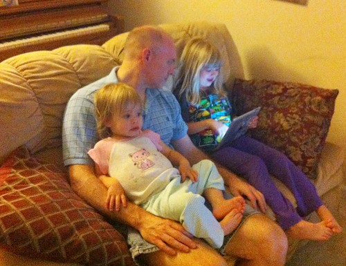 Lucy watches Bubble Guppies on The Guy's lap while Catie shows him her iPad game. #love
