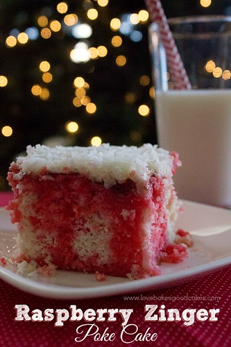 Raspberry Zinger Poke Cake on plate with a glass of milk.