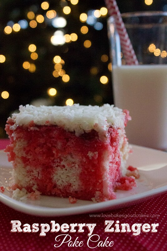 Raspberry Zinger Poke Cake on a plate with a glass of milk.
