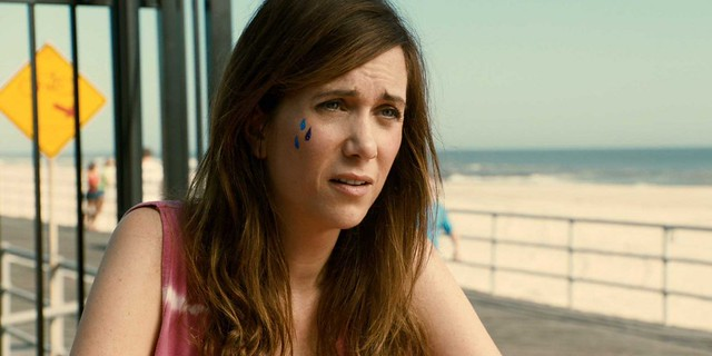 Kristin Wiig on a beach with tears painted on her cheek