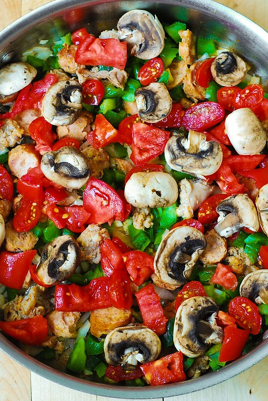 adding mushrooms to the pasta skillet with vegetables