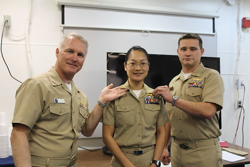 SAN DIEGO - Vice Adm. Thomas S. Rowden (left), Commander, Naval Surface Forces, takes part in a promotion ceremony for Lt Cmdr.  Nellie Wang (center), USS Pearl Harbor's (LSD 52) chief engineer, with the assistance of Lt. Cmdr. David Starnes (right).