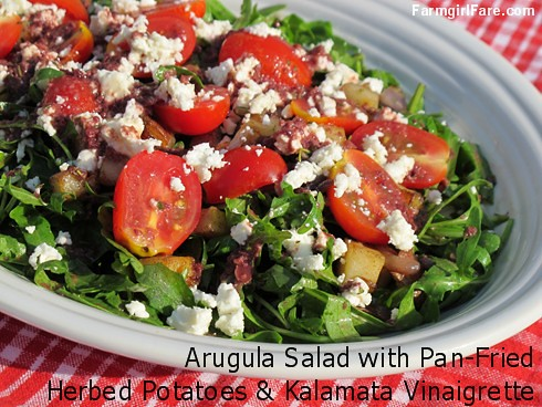 Arugula salad with pan-fried herbed potatoes, cherry tomatoes, feta cheese, and kalamata olive vinaigrette - FarmgirlFare.com