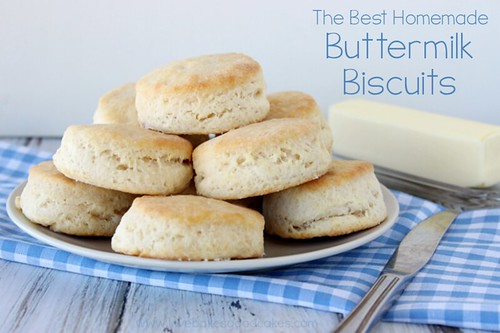 The Best Homemade Buttermilk Biscuits stacked up on a plate with a stick of butter and a butter knife.