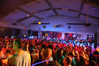 Students gather in a large hall lit by party lights.