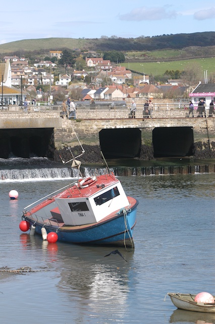 Single fishing boat on Mud and water in West Bay Marina, Dorset