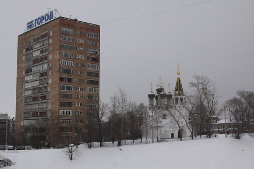 Soviet-era apartments tower over a historic church