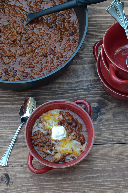An over the top shot of a red bowl full of Halftime Chili topped with sour cream and cheese.