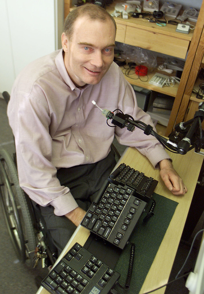 Gary Birch, Executive Director of the Neil Squire Foundation, sits with a couple of pieces of modified office equipment used to aid the disabled at the workplace. (BIV PHOTO/Richard Lam)