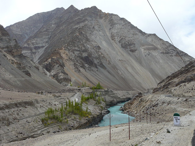 The Indus flowing through a gorge bordered by poplars, with rocky mountains in the background