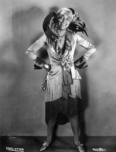 Ethel Waters, a black singer, wearing a fancy dress with giant feathers in the back