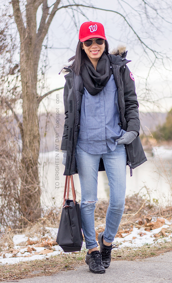 red cap, black infinity scarf, black parka, chambray shirt, black sneakers