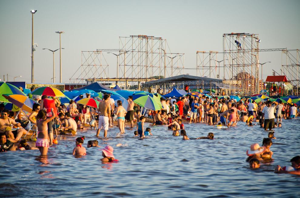 Bañistas disfrutan de las aguas del Río Paraná en la Playa San José mientras en el fondo está siendo construido un enorme escenario donde se llevaría a cabo el festival de música Personal Fest. (Elton Núñez)