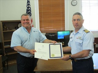 U.S. Coast Guard Capt. Ric Rodriguez (right), commander of Coast Guard Sector Charleston, S.C., accepts the official, historical documents Monday, May 12, 2014, in Charleston, that renamed a portion of the Charleston Harbor in 2008 to honor a retired U.S. Coast Guard admiral. Gary Santos (left), the port manager for Inchcape Shipping Services in Charleston, presented the documents to Rodriguez. U.S. Coast Guard photo.