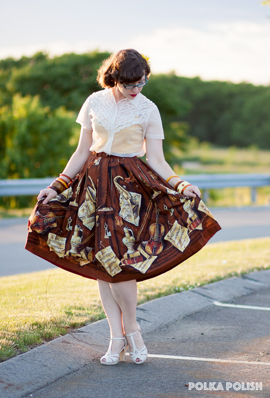 A simple 1950s outfit serves to set off a novelty print skirt featuring a still life with musical instruments