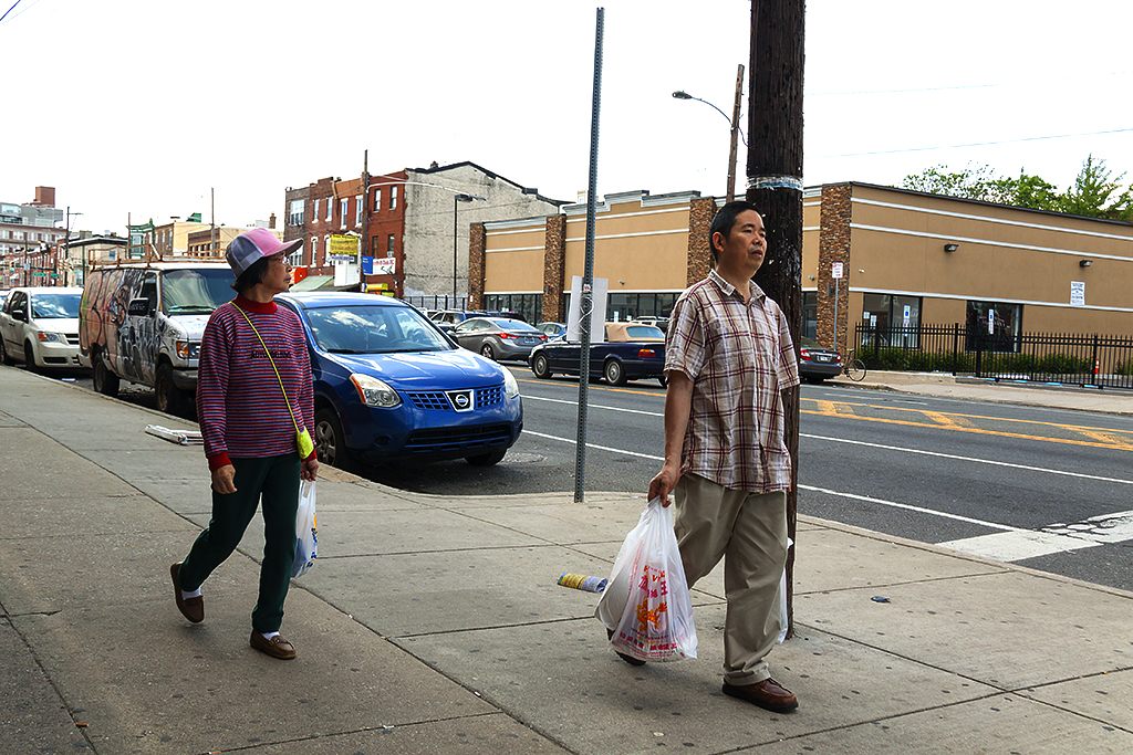 Chinese couple walking down Washington Avenue--Italian Market