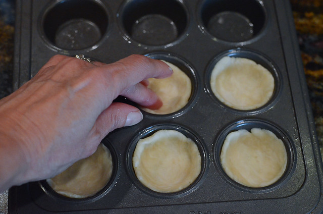 Fingers press into dough to shape it into a mini muffin pan.