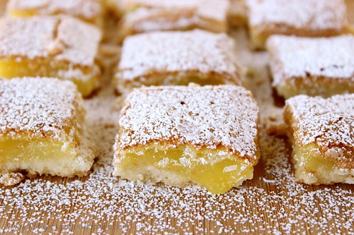 The BEST Lemon Bars EVER. Lemon bars cut into squares with powdered sugar close up.