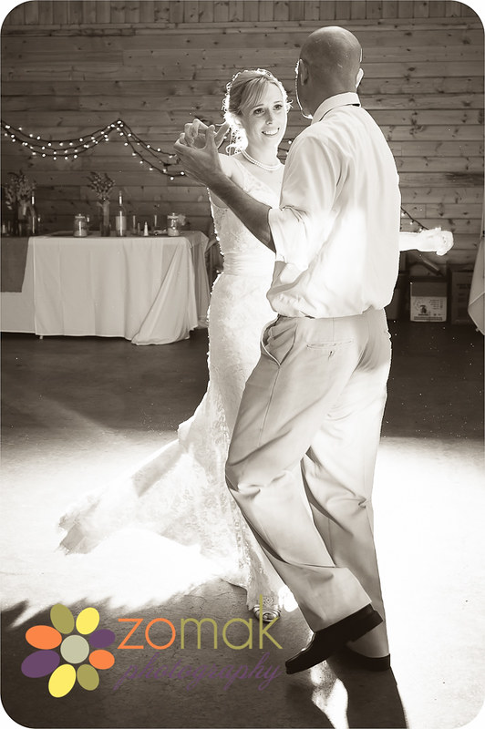 Backlit black and white image of bride and groom dancing at their wedding reception.