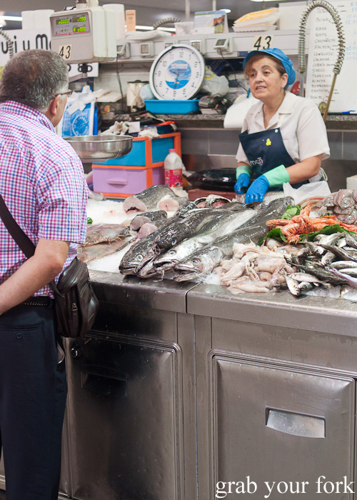 Fishmonger with a shopper at Plaza de Lugo Fish Market in A Coruna, Galicia, Spain