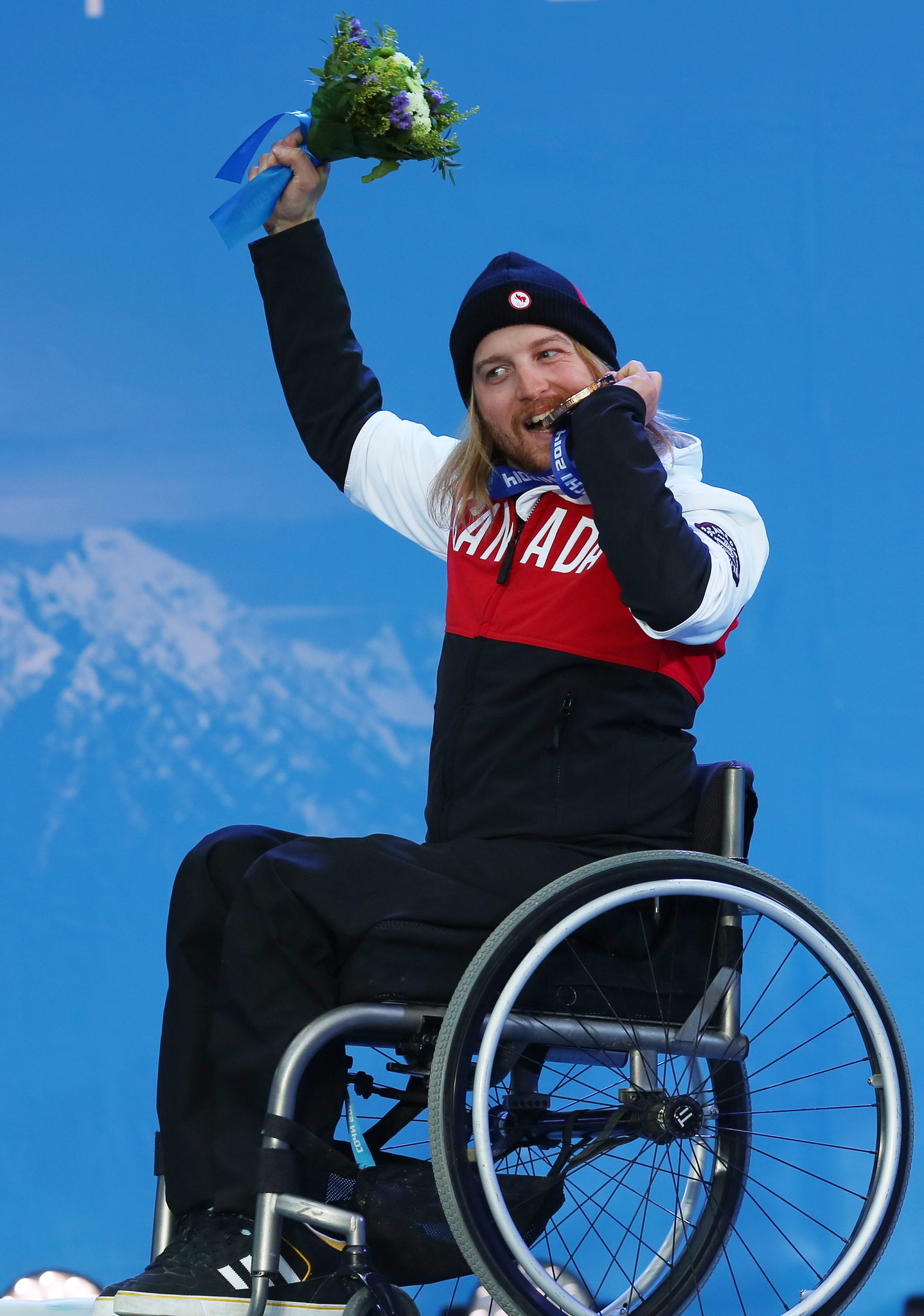 Brousseau takes a bite of his Paralympic bronze medal in Sochi, RUS