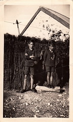 Portrait of two boys against a ti-tree fence (undated)