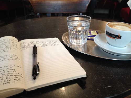 A cup of coffee, an open journal, and a pen on a cafe table