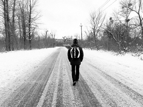 Image of a person walking down a path in winter.