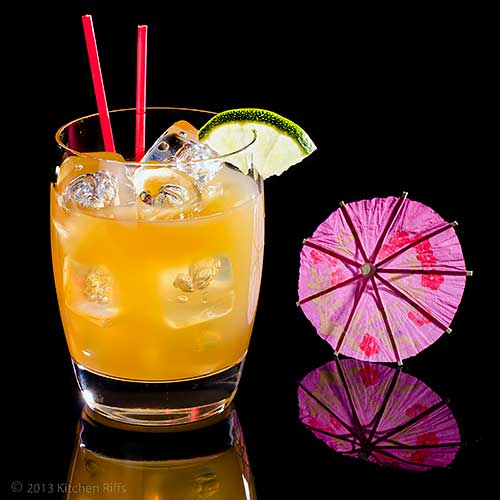 Volcano Bowl Cocktail in glass with lime garnish and cocktail umbrella