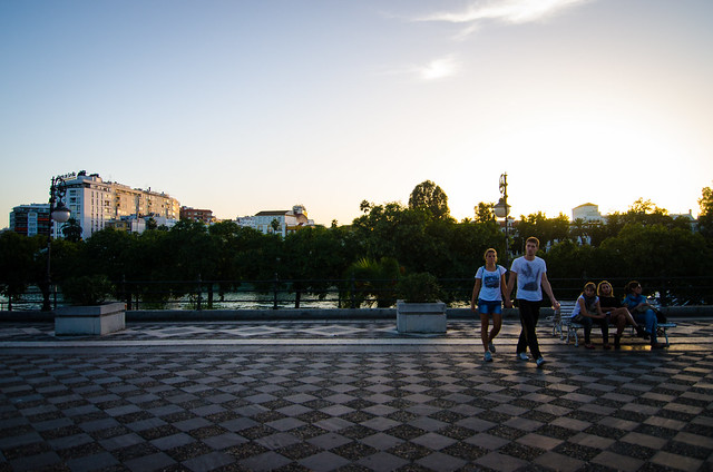 A  sunset walk along the checkered sidewalk near Sevilla's Guadalquivir River.
