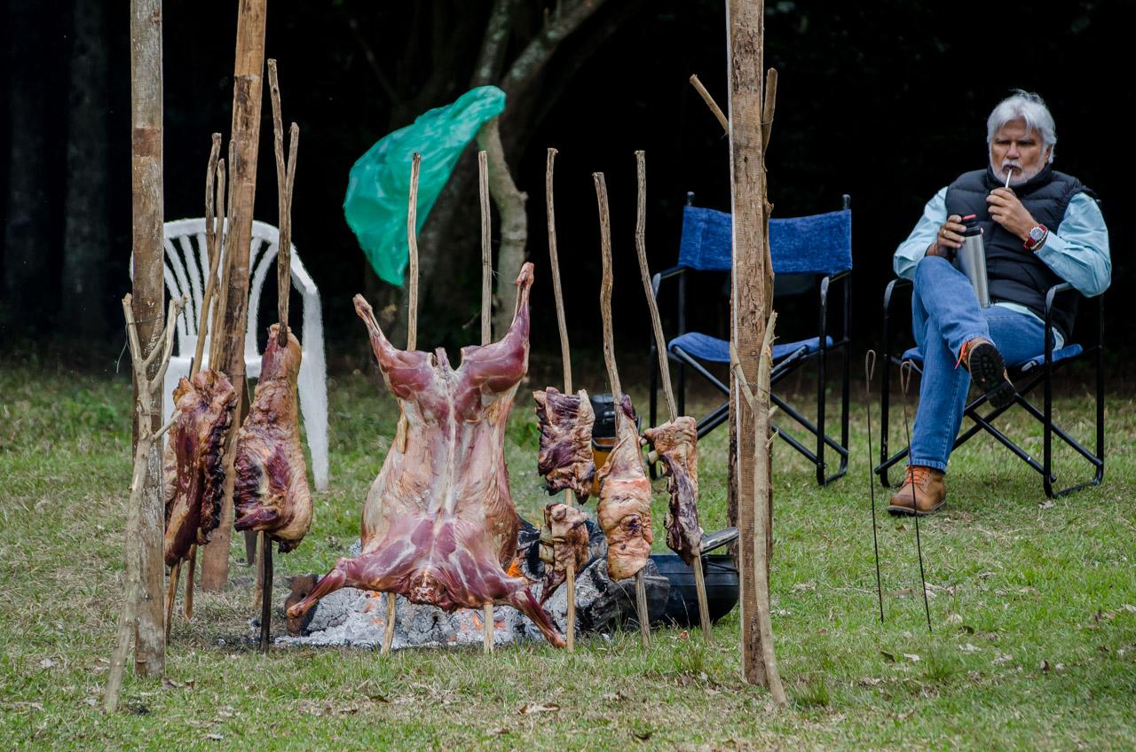 Un miembro de la estancia La Escondida toma mate mientras vigila la cocción del asado a la estaca durante la jineteada que se realizó el pasado 26 de junio en las afueras de la ciudad de San Juan. (Elton Núñez)