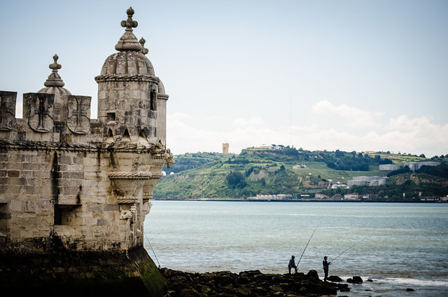 Locals fish from the River Tagus at the base of Torre de Belém in Lisbon, Portugal.