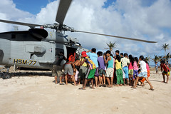 Local residents in Guiuan approach an MH-60R Seahawk from Helicopter Maritime Strike Squadron (HSM) 77 as it delivers relief supplies Nov. 17 during Operation Damayan. (U.S. Navy photo by Mass Communication Specialist 3rd Class Peter Burghart)