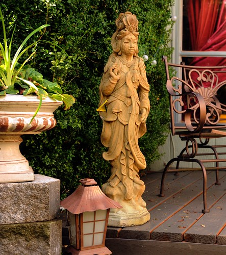 Standing female bodhisattva statue in traditional robes against a green bush observing the fall's fast approach, Japanese lantern, planter, deck, patio chairs, window curtains, A Garden for the Buddha, Seattle, Washington, USA by Wonderlane