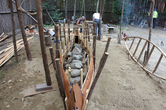 Craftsmen build a canoe using traditional methods at the museum