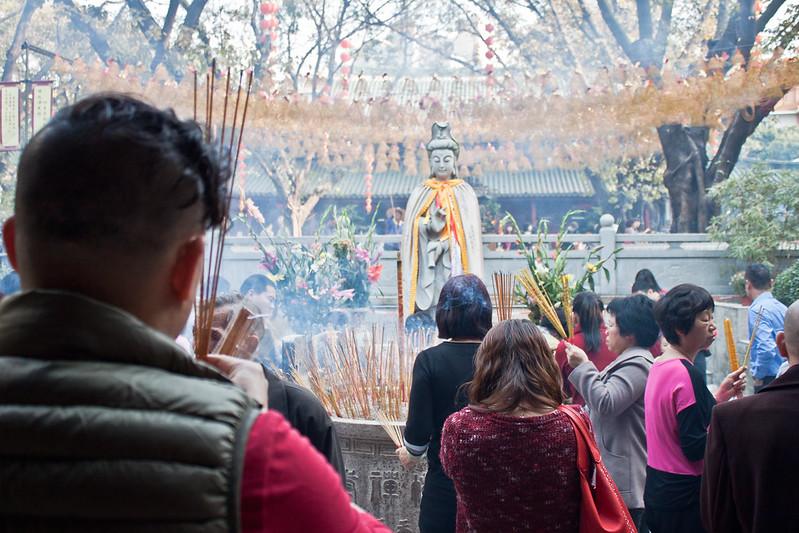 Gente rezando con inciensos ante la estatua de una diosa en el templo de Haitang.
