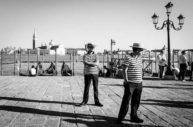 Iconically dressed Gondoliers bark for customers in front of the Grand Canal in Venice.