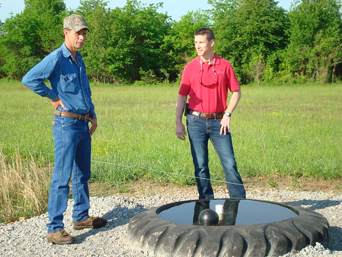 Dale Courtney (left) visits with Randolph County NRCS District Conservationist Adam Eades near an electric fence and tire tank watering facility about the resilience a good prescribed grazing program offers during a drought.