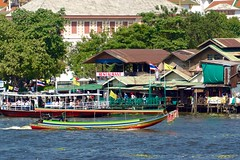 Longtail or dragon boat on the Chao Phraya river passing Tha Thien pier seen from Wat Arun, the temple of dawn, in Bangkok, Thailand