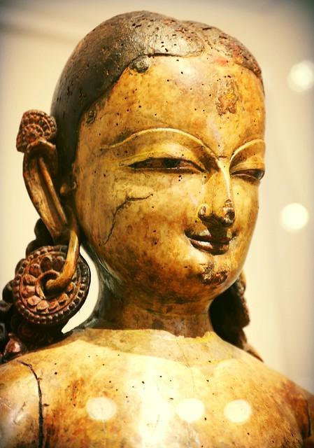 Lady Tara the savior, detail of statue, smile, earrings pinned through ear, 15th century, wood, Kathmandu Valley, Patan, Art Institute, Chicago, Illinois, USA