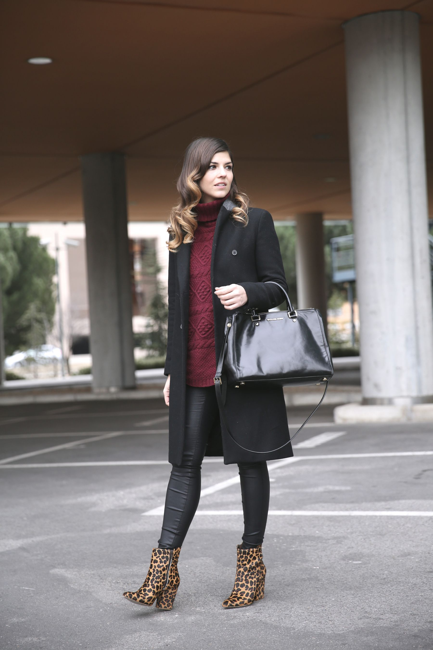 Look casual con leggings de cuero, jersey burgundy de punto, abrigo negro y botines con animal print