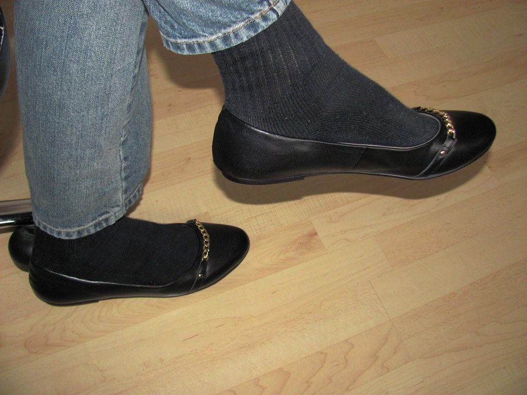 If women (especially when wearing pants) need to wear their pumps or flats with some kind of socks, I think they would look better (and perhaps feel more confortable) with regular covering socks (for example, trouser socks), of the color, thickness and material that best suit their look and confort.
