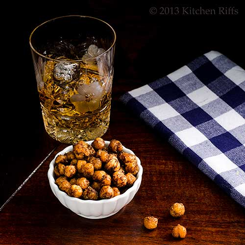 Spicy Roast Chickpeas in small ramekin with cocktail in background