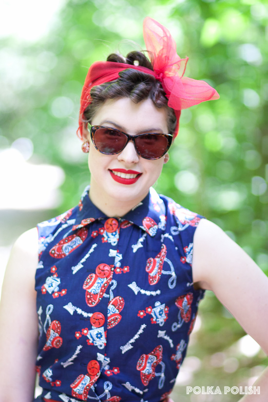 Big cat-eye sunglasses, red lipstick, and a chiffon scarf over pin curls make even a casual outfit look glamorous