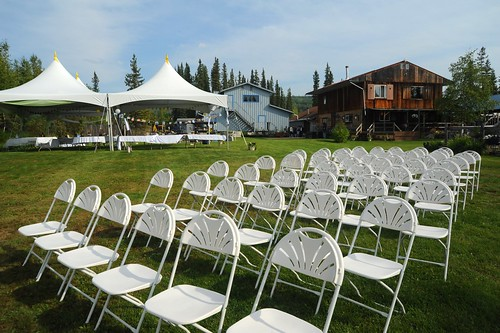 Seats and tents set up for the open air wedding in a grassy green field, log house, Wedding of Jessie and Chris, summer, Fairbanks, Alaska, USA by Wonderlane