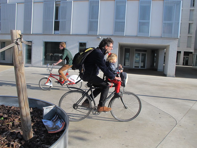 Child transported by father on bicycle
