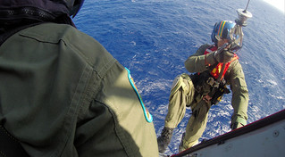 "A Coast Guard rescue swimmer is hoisted down to the Norwegian Getaway cruise ship from an MH-65 Dolphin helicopter from Air Station Borinquen, approximately 90 nautical miles northwest of Puerto Rico, to assess the condition of a 13-year-old boy requiring medical attention ashore Feb. 16, 2015. The boy, his mother and cruise ship doctor were hoisted aboard the aircraft via rescue basket and transported to the Isla Grande Airport, where the patient was received by Emergency Medical Services personnel and transported to the ""Centro Medico"" Hospital in San Juan, Puerto Rico. (U.S. Coast Guard photo)"